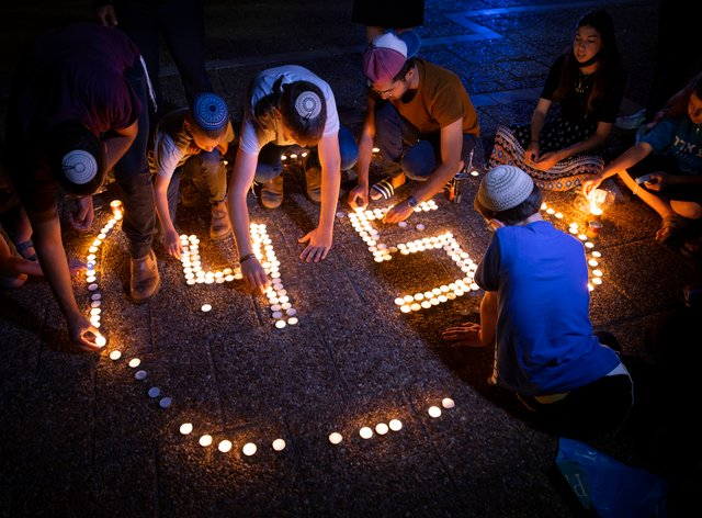 Israeli youths light candles in memory of the 45 ultra-Orthodox Jews killed in a stampede at a religious festival on Friday, during a vigil in Tel Aviv, Israel