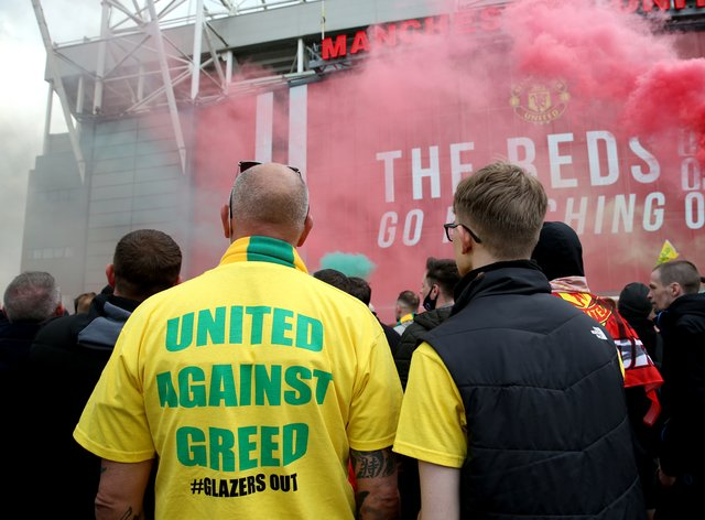 """A fan wears a shirt with a """"United Against Greed"""" message on it"""