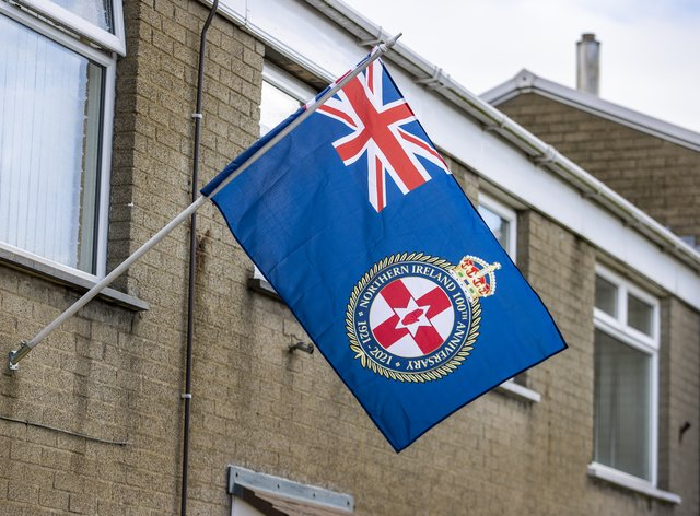 A Northern Ireland 100th Anniversary flag flickers in the wind from a flagpole attached to a house close on the Longstone Road area of Lisburn