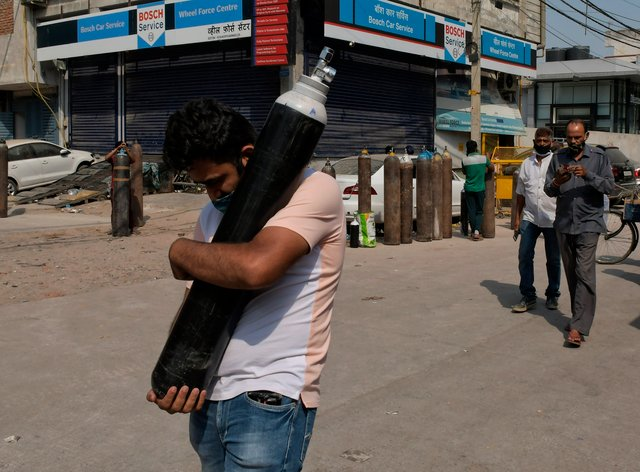 A man walks carrying a refilled cylinder as family members of Covid-19 patients wait in queue to refill their oxygen cylinders at Mayapuri area in New Delhi, India