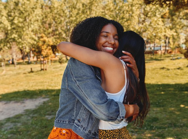 Two friends hugging in a park