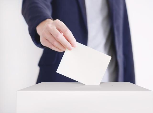 Man putting a ballot into a voting box