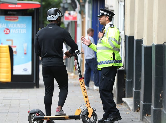 A police officer talks to an e-scooter rider