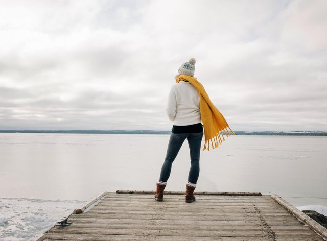 woman standing on the end of a pier