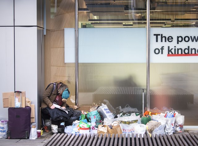 A homeless person sits in a window in the City of London. (Victoria Jones/PA)