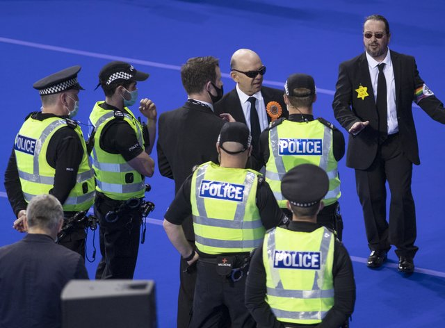 Police speak with members of the Liberal Party before they are removed from the count floor