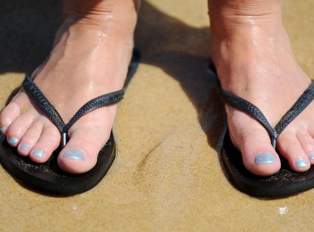 A woman wearing flip flops on a beach