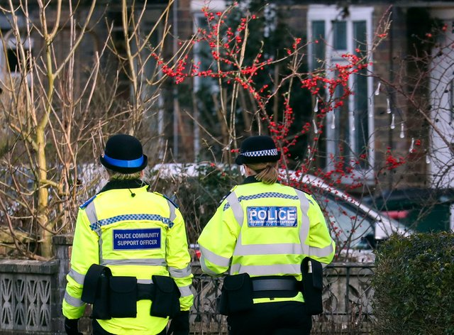 A Sussex police officer and a Community Support Officer walk along a street in Crawley, Sussex