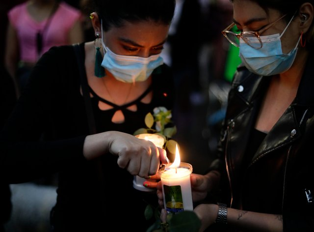 A woman lights a candle during a march demanding justice for the people who died in Monday's subway collapse, in Mexico City's south side