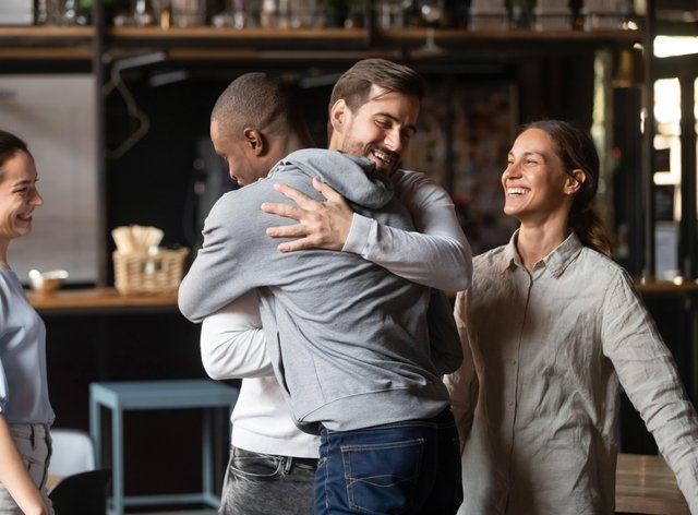 Two friends hugging in a restaurant