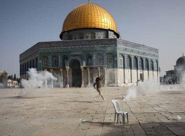 A Palestinian man runs away from tear gas during clashes with Israeli security forces in front of the Dome of the Rock Mosque at the Al Aqsa Mosque compound in Jerusalem's Old City