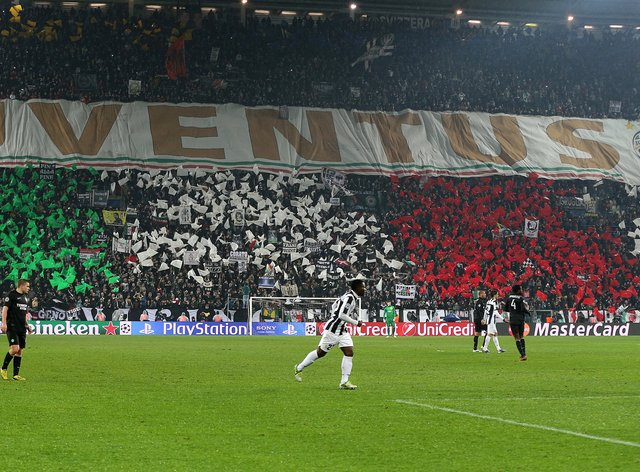 Juventus fans hold a giant banner and flags bearing the colours of the Italian national flag