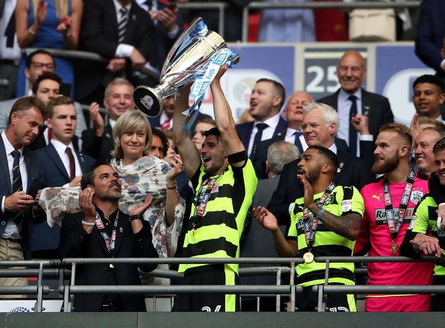 Christopher Schindler, holding trophy, helped Huddersfield win promotion to the Premier League via the play-offs in 2017
