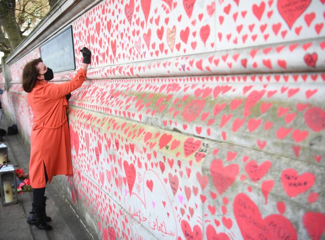 Fran Hall, who lost her husband to coronavirus, takes part in the final stages of painting approximately 150,000 hearts on the Covid memorial wall on the Embankment in London (Victoria Jones/PA)