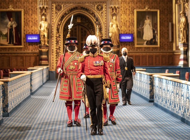 Masked Yeoman Warders march along the Royal Gallery during the ceremonial search of the Palace of Westminster ahead of the State Opening of Parliament by the Queen