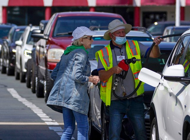 A customer helps pumping gas at Costco, as other wait in line