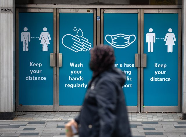A person wearing a face mask walks past Covid safety guidance notices