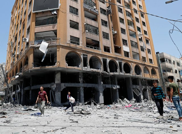 People inspect the rubble of a damaged building which was hit by an Israeli air strike in Gaza City