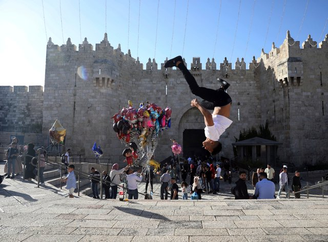 A Palestinian youth performs a back flip at the Damascus Gate to the Old City of Jerusalem as people gather for Eid al-Fitr, marking the end of the Muslim holy month of Ramadan