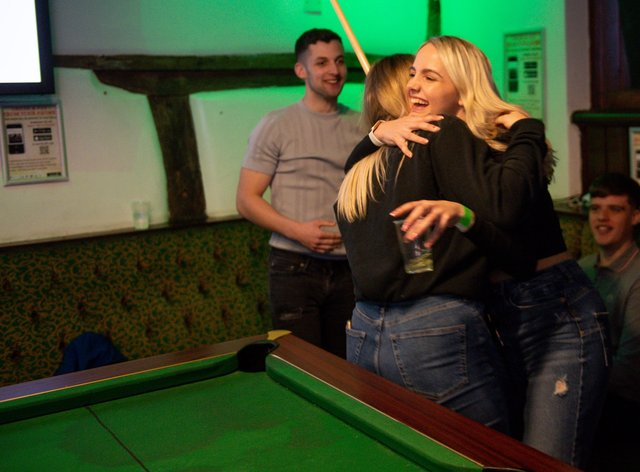 Customers enjoy a game of pool and a hug at the The Oak Inn in Coventry (Jacob King/PA)