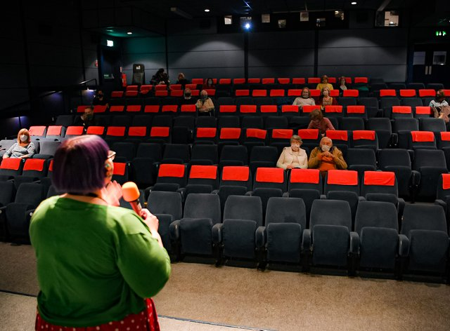 Cinema programme manager Claire Vaughan introduces the film Nomadland to audiences inside a movie theatre screen at Chapter, Cardiff