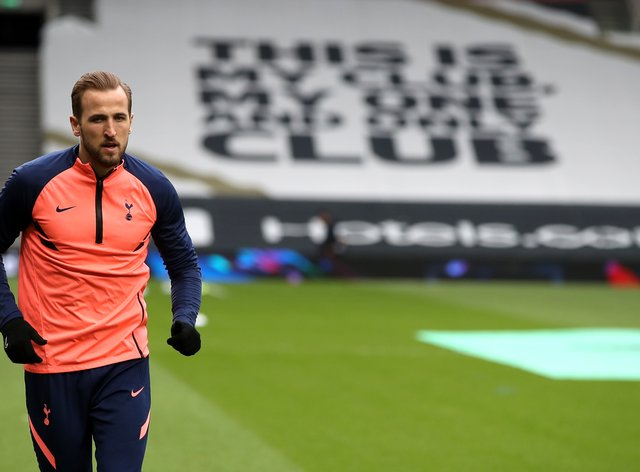 Harry Kane warms up in front of a Tottenham banner reading 'This is my club, my one and only club'