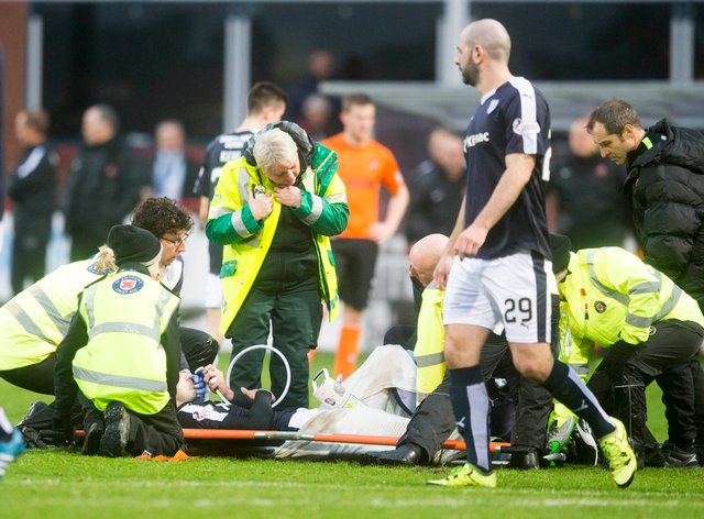 James McPake lies on a stretcher on the pitch