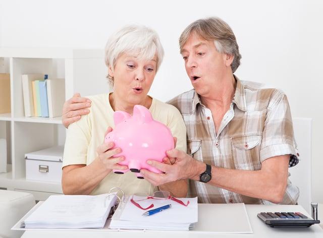 Senior Couple Saving Money In The Pink Piggybank