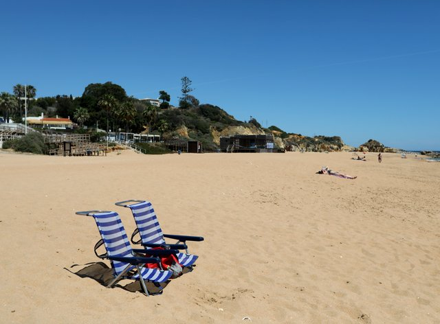 Two chairs rest on the sand at a nearly empty beach in Albufeira, in Portugal's southern Algarve region
