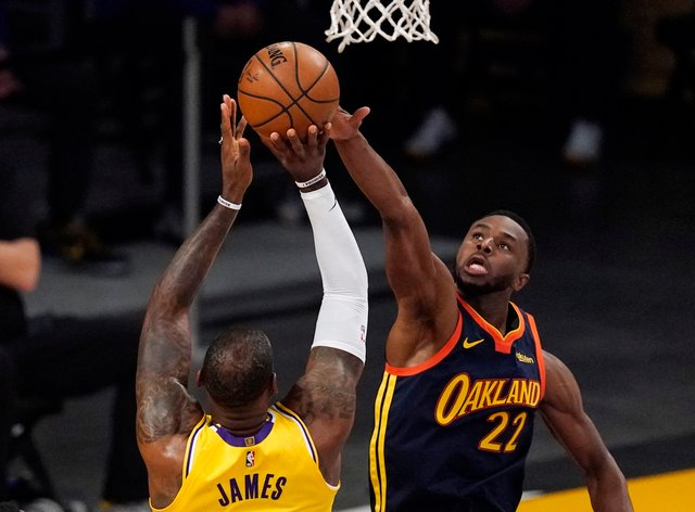 Los Angeles Lakers forward LeBron James, left, has his shot blocked by Golden State Warriors forward Andrew Wiggins