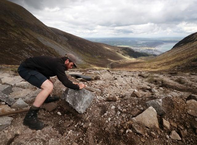 National Trust mountain ranger Theo Burke trails heavy slabs up Slieve Donard