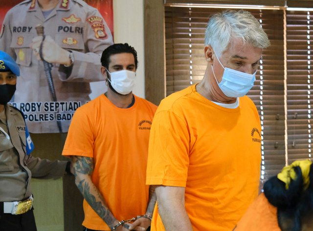 British national Kenneth Daniel Kutsch, right, and Italian national Francesco D'alesio are shown to the media during a police press conference in Badung, Bali, Indonesia