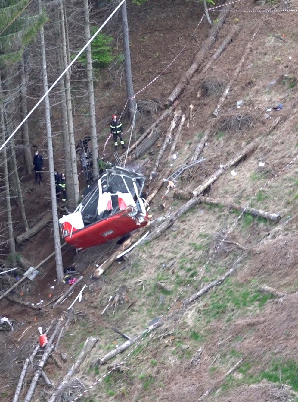 Rescuers work by the wreckage of a cable car after it collapsed near the summit of the Stresa-Mottarone line in the Piedmont region, northern Italy