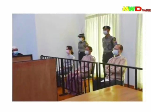 In this image from Myawaddy TV, a photograph shown during a news report showing the appearance of deposed Myanmar leader Aung San Suu Kyi, former president Win Myint, sitting 3rd from right, and former Naypyitaw Council chairman Dr. Myo Aung before a special court, shown while a report about Suu Kyi's case is read by a news presenter in Naypyitaw, Myanmar