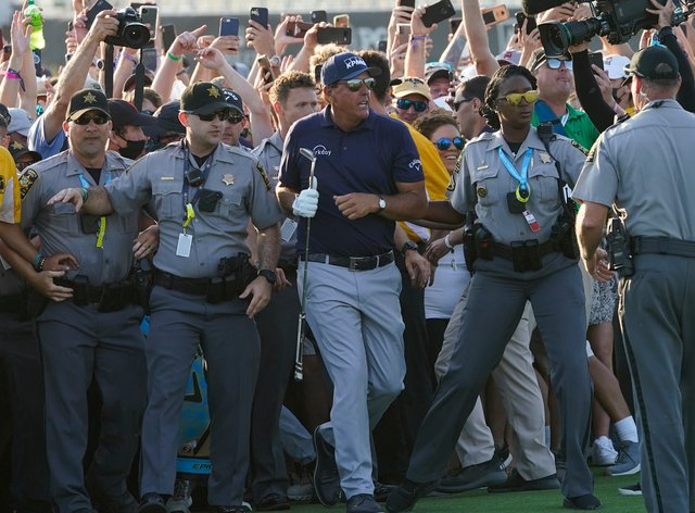 Phil Mickelson wades through fans on the 18th fairway
