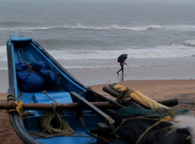 A man walks holding an umbrella on a beach on the Bay of Bengal coast in Odisha, India