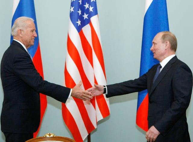 Joe Biden shakes hands with Vladimir Putin