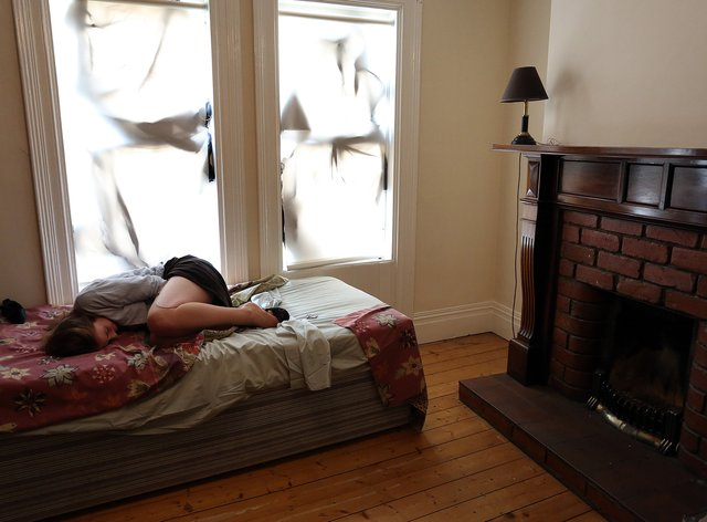 A woman shelters looking scared on a bed