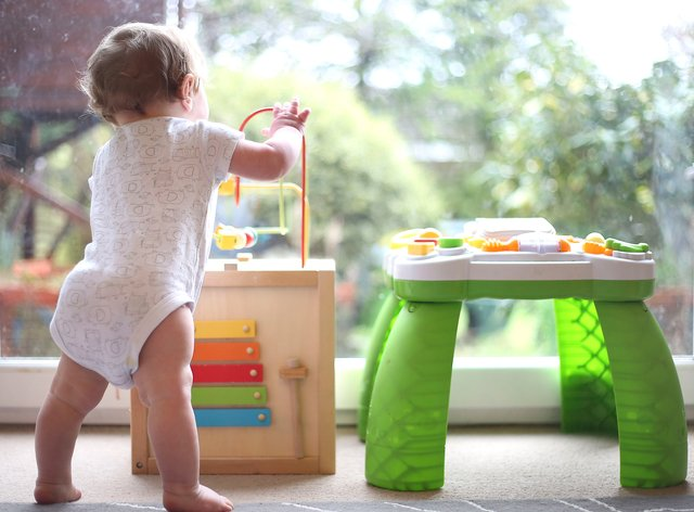 A baby boy playing with an activity table