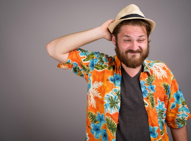 Young bearded tourist man ready for vacation against gray backgr