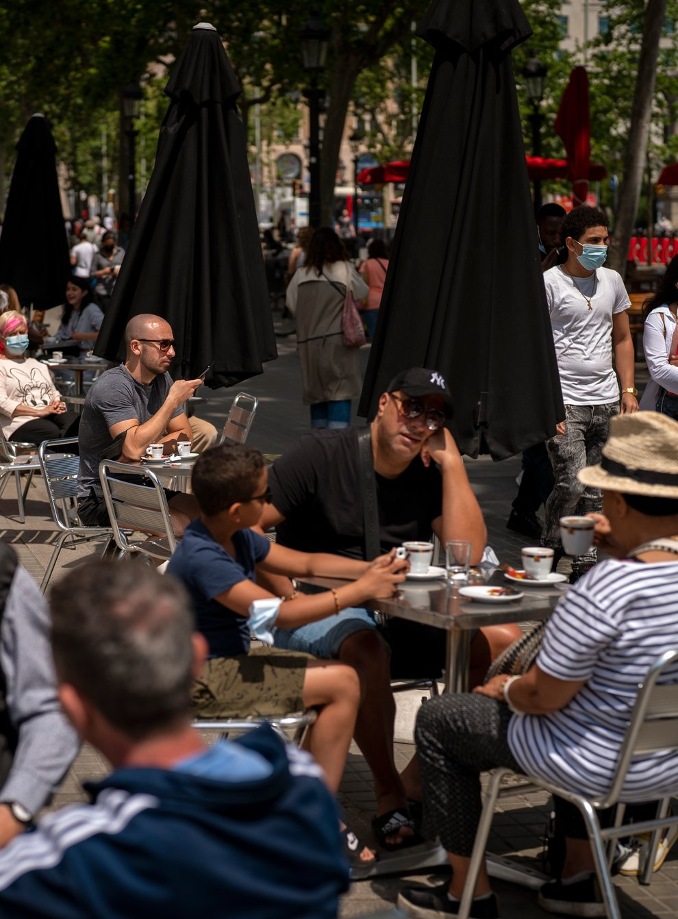 <p>Customers at a terrace bar in Barcelona</p>