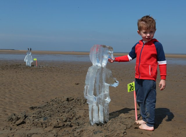 Toby Heptinstall, three, looks at one of 26 ice sculptures of children installed on New Brighton Beach, Wallasey in Merseyside
