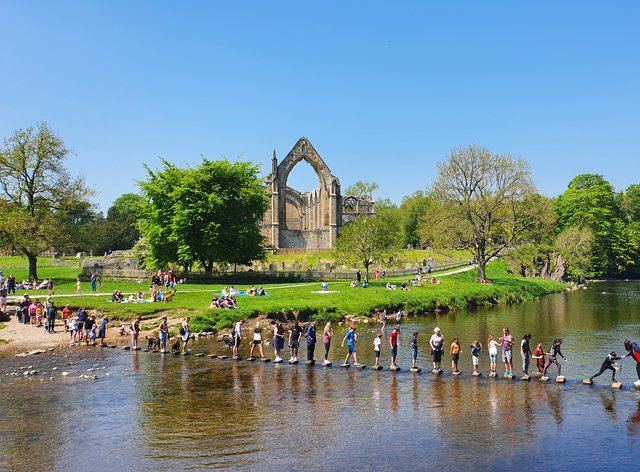 Tackling the stepping stones at Bolton Abbey in North Yorkshire