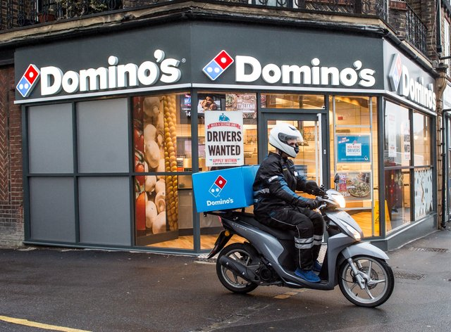 A delivery rider outside a branch of Domino's Pizza