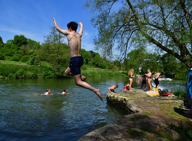 Swimmers enjoy the hot weather at Warleigh Weir, Bath
