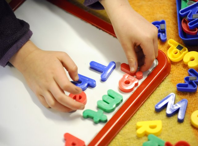 A child plays with magnetic letters