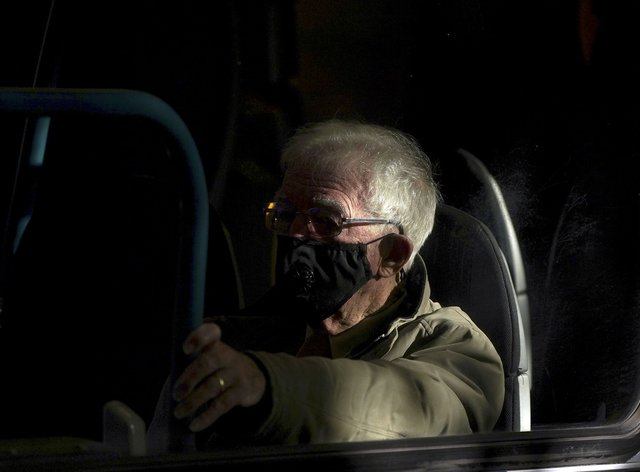 A man wears a mask on a bus