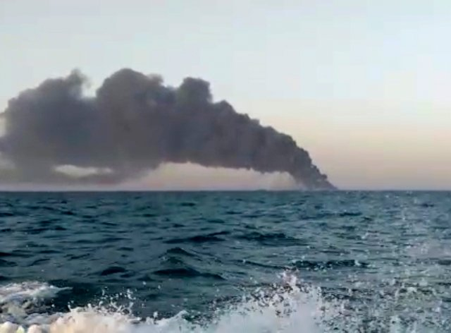 Smoke rising from Iran's navy support ship Kharg in the Gulf of Oman (AP)