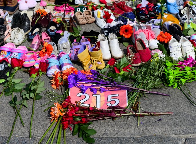 Flowers, children's shoes and other items at a memorial at the Eternal flame on Parliament Hill in Ottawa