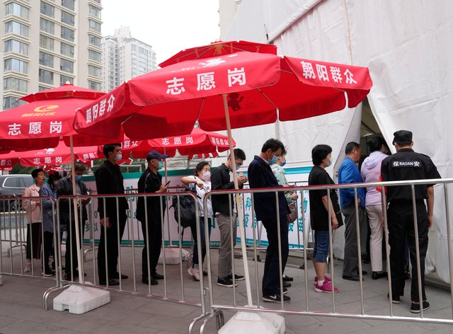 Residents line up outside a vaccination centre in Beijing
